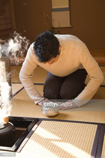 Man attending Japanese tea ceremony, bending over, front view, Japan