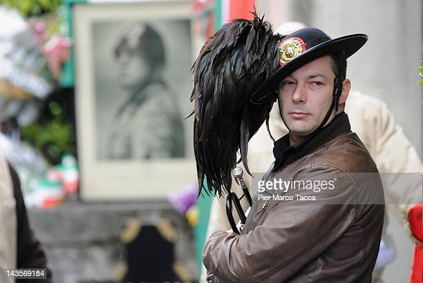 A man attends a commemoration ceremony for the death of Italian dictator Benito Mussolini and his mistress Claretta Petacci in front of a headstone...