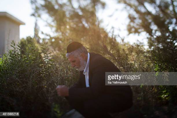 A man attends the funeral ceremony held for the three Israeli teenagers found dead on July 1 2014 in Modiin Israel The bodies of Eyal Yifrah Gilad...