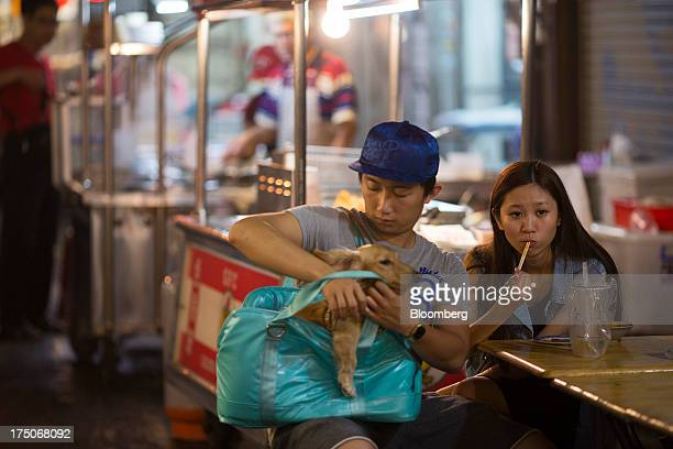 A man attends to a dog in a bag while a woman eats a snack at a food stall in Tong Hua market in Taipei Taiwan on Friday July 26 2013 Taiwans economy...