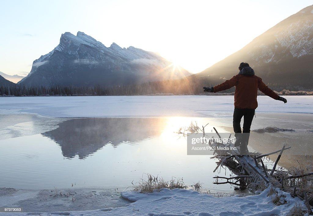 Man balances across log over partly frozen lake : Stock Photo