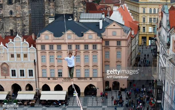 A man balances on a rope attached highly over the Old Town square as part of the 'Zivot na hrane' campaign supporting people diagnosed with diabetes...