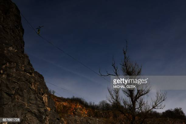 TOPSHOT A man balances on a rope during a slackline festival in a quarry near Beroun central Bohemia Czech Republic on March 25 2017 / AFP PHOTO /...