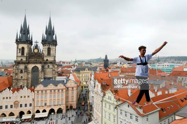 TOPSHOT A man balances on a rope highly over the Old Town square as part of the 'Zivot na hrane' campaign supporting people diagnosed with diabetes...