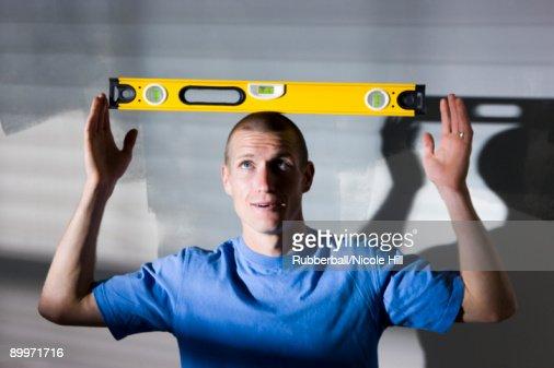 man balancing a level on his head