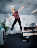 Man balancing at the edge of his office table.