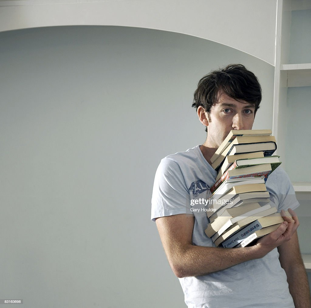 Man balancing big stack of books with one hand : Stock Photo