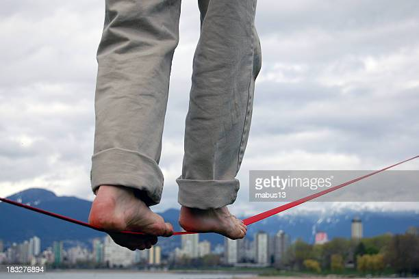Man balancing on a red tightrope in bare feet