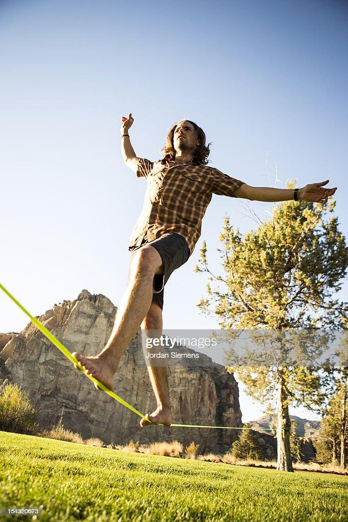 A man balancing on a slackline. : Stock Photo