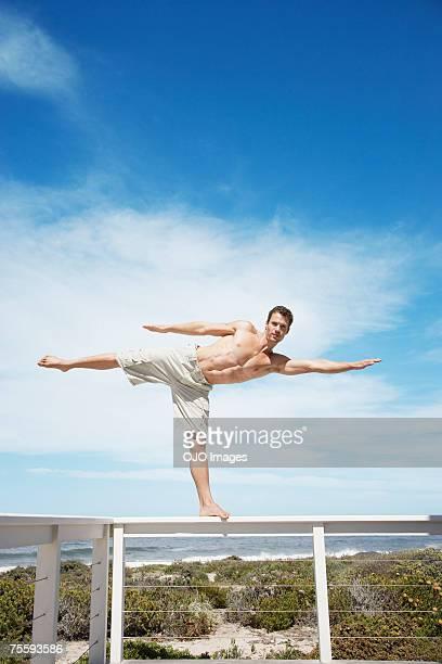 Un homme en équilibre sur le rail d'une terrasse