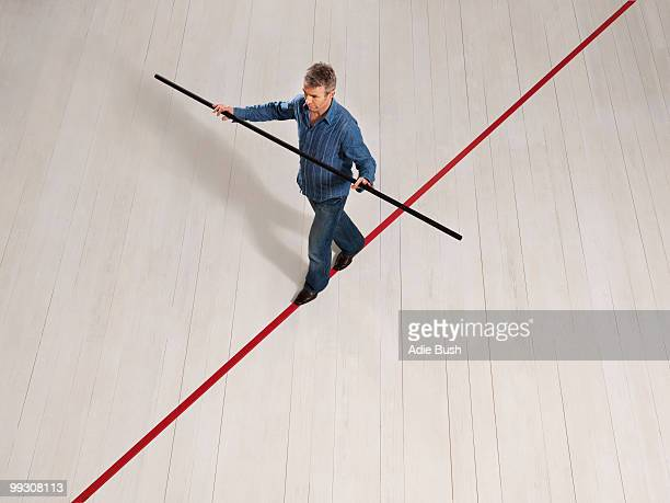Man balancing on thin red line with pole