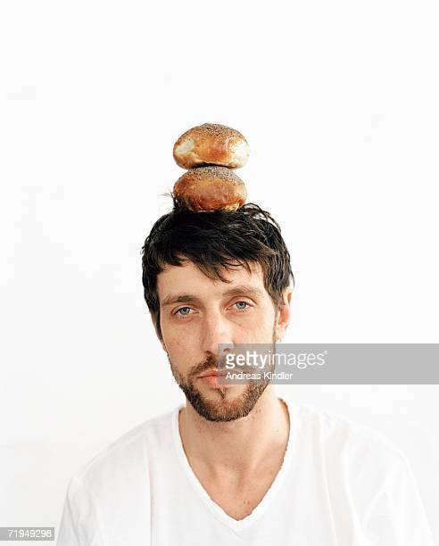 A man balancing two buns on his head.