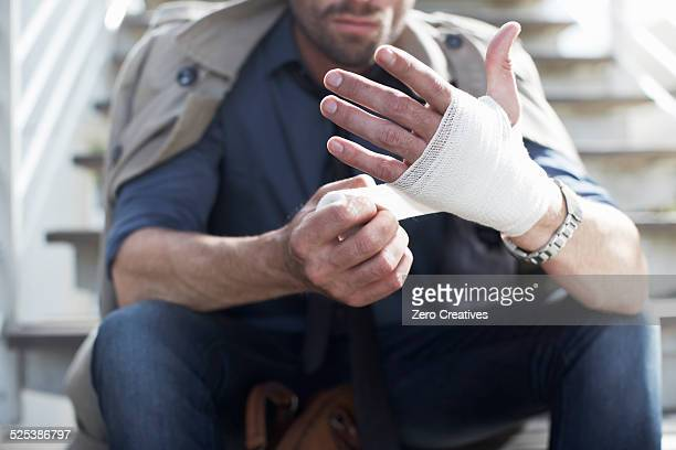 Man bandaging hand on staircase
