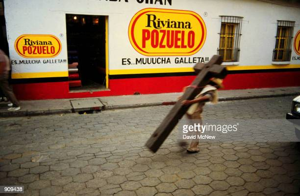 A man bares a solid wood crosslike structure which is the base for a goods display to market in Chichicastenango in the Western Highlands of Guatemala