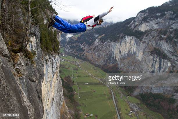 Man BASE jumping from a cliff into a valley below