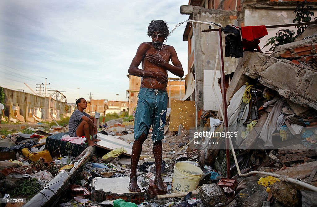 A man bathes from a small hose amongst the remains of demolished homes in the Metro Mangueira favela, located near Maracana stadium, on May 22, 2014 in Rio de Janeiro, Brazil. The homes were thought to have been knocked down for a parking lot for the stadium, though that has yet to be built. The area has seen some people occupy certain dwellings. Evictions and demolitions have been occurring in Rio favelas ahead of the 2014 FIFA World Cup and Rio 2016 Olympic Games in spite of a housing shortage in the city. Rio's housing and urban planning goals include a planned five percent reduction of areas occupied by favelas by 2016. Alternative affordable housing, generally on the peripheries of the city, is unable to meet demand and some residents complain they have not received adequate compensation for demolished homes.