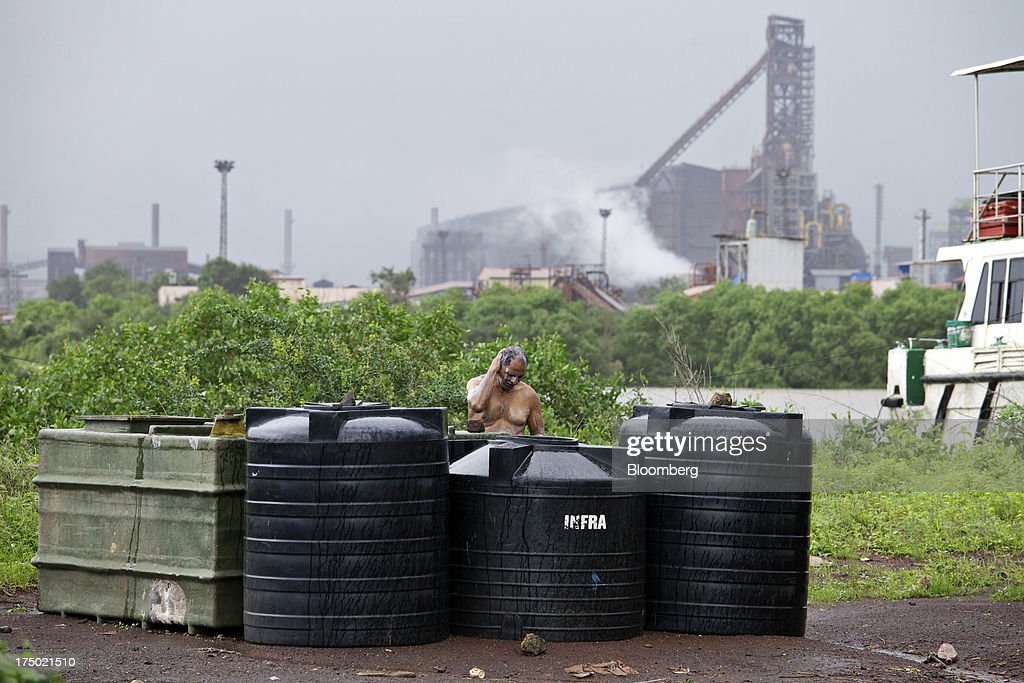 A man bathes in front of the JSW Steel Ltd. manufacturing facility in Dolvi, Maharashtra, India, on Friday, July 27, 2013. JSW Steel is scheduled to announce first-quarter earnings on July 31. Photographer: Adeel Halim/Bloomberg via Getty Images
