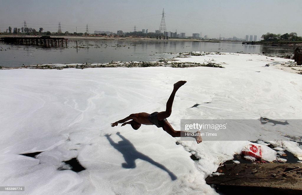 A man bathes in river Yamuna at Kalindi Kunj on March 9, 2013 in New Delhi, India. Yamuna in Delhi is almost dead with water not suitable for even bathing at most places, leave along supporting aquatic life. It is mainly due to high ammonia level emanating from high discharge of industrial pollutants in the river.
