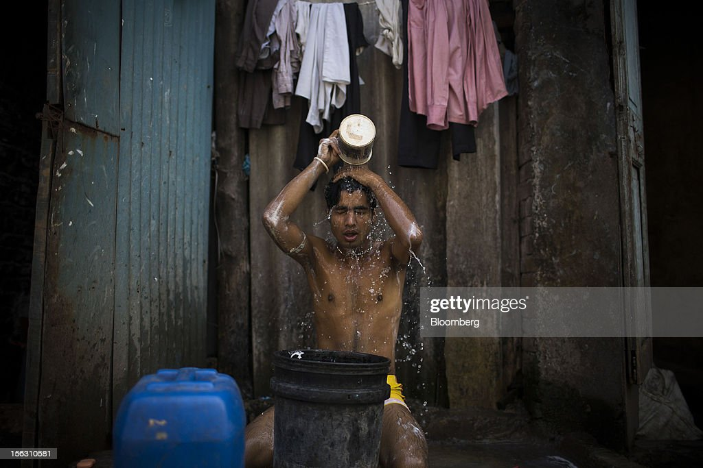 A man bathes in the Dharavi slum area of Mumbai, India, on Friday, Nov. 9, 2012. Indian industrial production unexpectedly fell in September and the trade deficit widened to a record last month as exports declined, adding to signs that Asia's third-largest economy is struggling. Photographer: Brent Lewin/Bloomberg via Getty Images