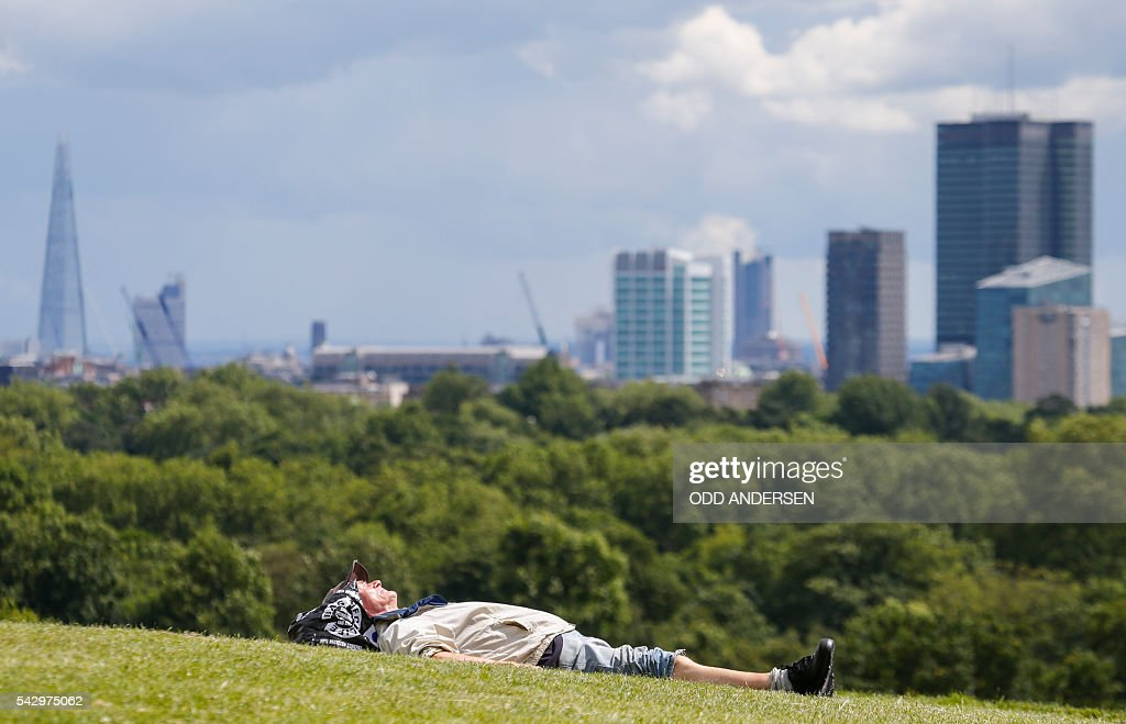 A man bathes in the sun as London landmarks, including the Shard, are pictured on the skyline, from Primrose Hill in north London on June 25, 2016, after the announcement that the UK had voted on June 23 to leave the European Union in a national referendum. The result of Britain's June 23 referendum vote to leave the European Union (EU) has pitted parents against children, cities against rural areas, north against south and university graduates against those with fewer qualifications. London, Scotland and Northern Ireland voted to remain in the EU but Wales and large swathes of England, particularly former industrial hubs in the north with many disaffected workers, backed a Brexit. / AFP / Odd ANDERSEN