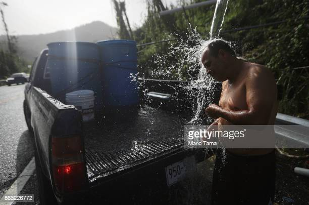 A man bathes with water funneled with pipes from a mountain spring after filling barrels of water for his home nearly one month after Hurricane Maria...