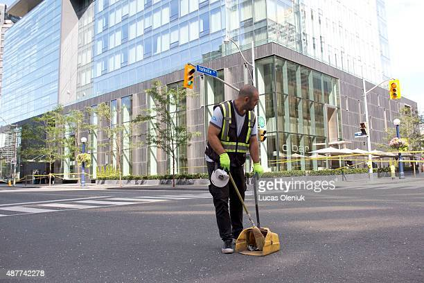 A man began to sweep glass of the street after shattered plane of glass rained down on Bay Street and Yorkville Avenue Thursday afternoon He was...