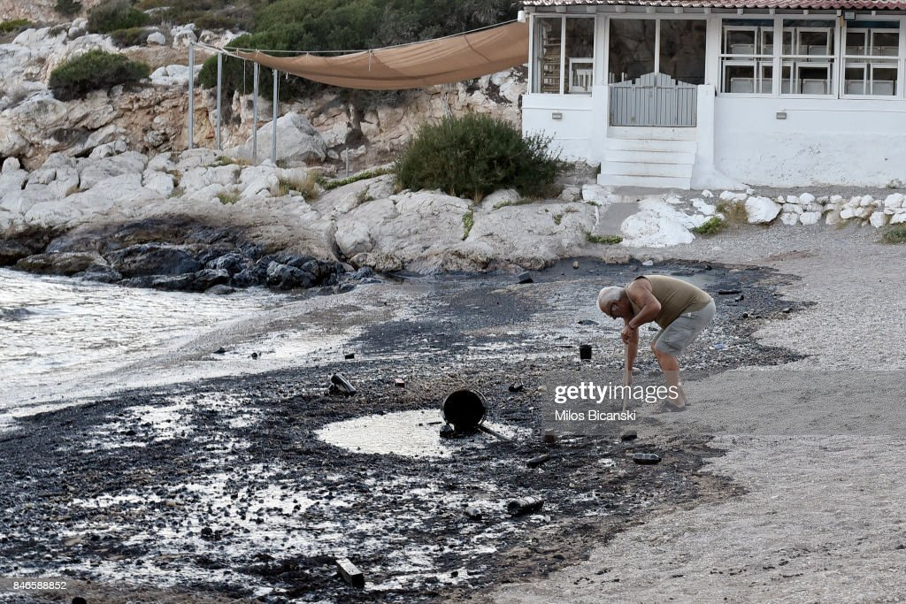 A man begins to clear oil from a polluted beach on the coast of Salamis Island on September 13, 2017 in Salamis, Greece. The small tanker 'Agia Zoni II' sank on September 10, whilst anchored off the coast of Salamis, near Greece's main port of Piraeus. It was carrying a cargo of 2,200 tons of fuel oil and 370 tons of marine gas oil. Salamis Island has suffered heavy pollution as a result in what has been called a 'major environmental disaster' by officials.