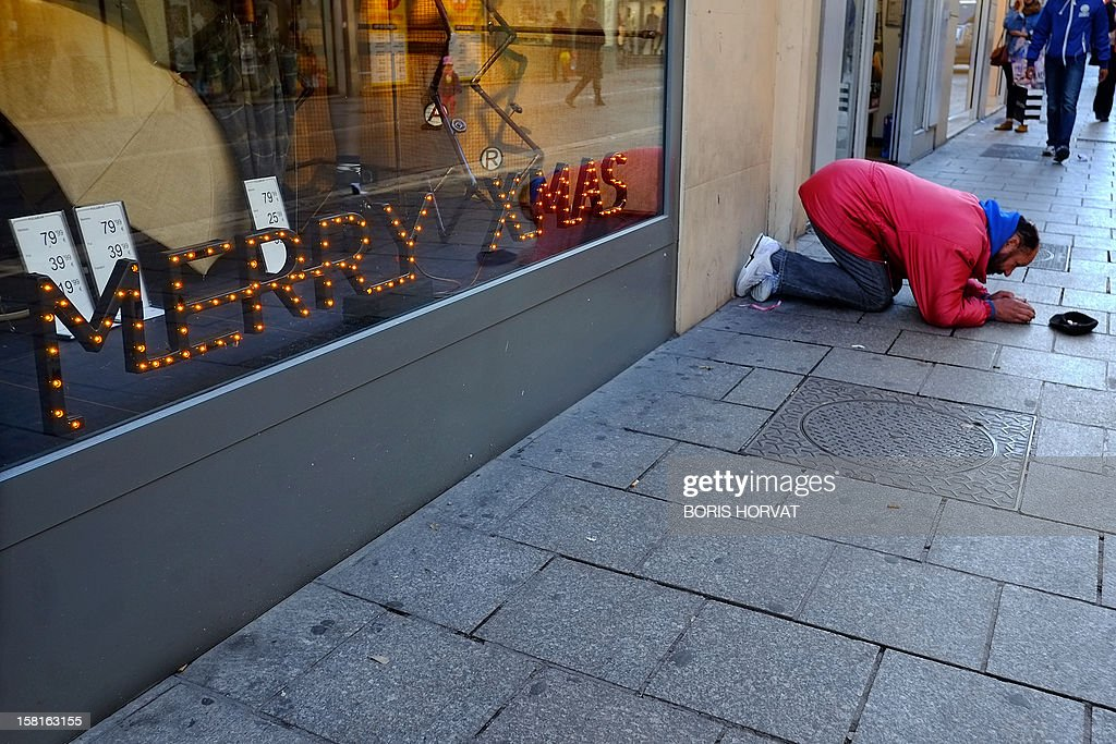 A man begs for money next to a shop window reading 'Merry Christmas' on December 10, 2012 in Marseille, southern France. Nearly one in two French people consider themselves poor or fear they soon will be, said a survey published ahead of a national poverty conference that comes amid a period of prolonged economic stagnation. AFP PHOTO / BORIS HORVAT