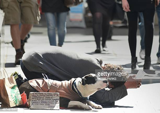 A man begs for money with his dog on a street in Sydney on September 10 2015 Australia's unemployment rate fell to 62 percent in August with...