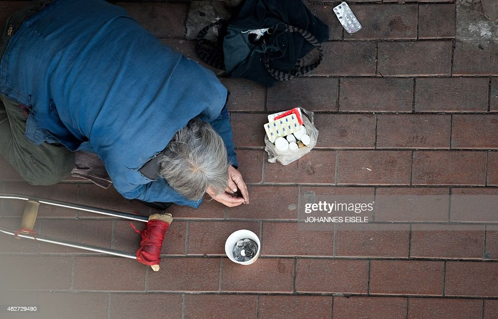 A man begs in front of Shanghai South Railway Station ahead of the Chinese Lunar New Year holidays in Shanghai on February 4 2015 The travel period...