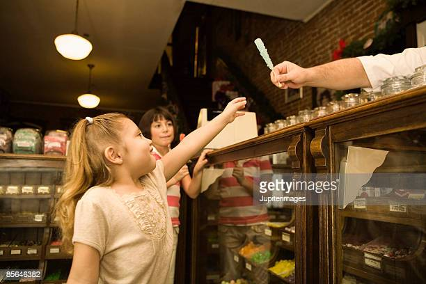 Man behind counter giving girl rock candy