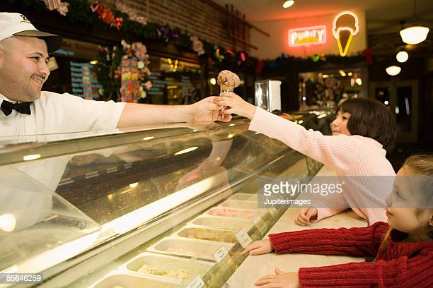 Man behind counter giving ice cream cone to girl