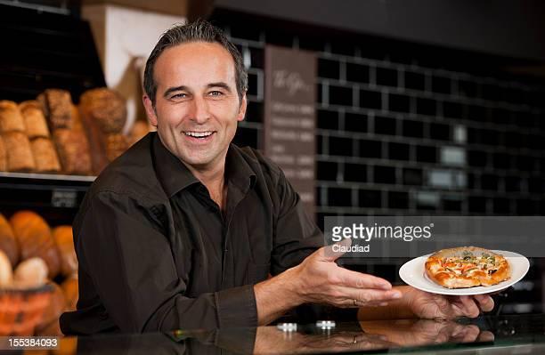 Mann hinter der Theke präsentiert kleine pizza