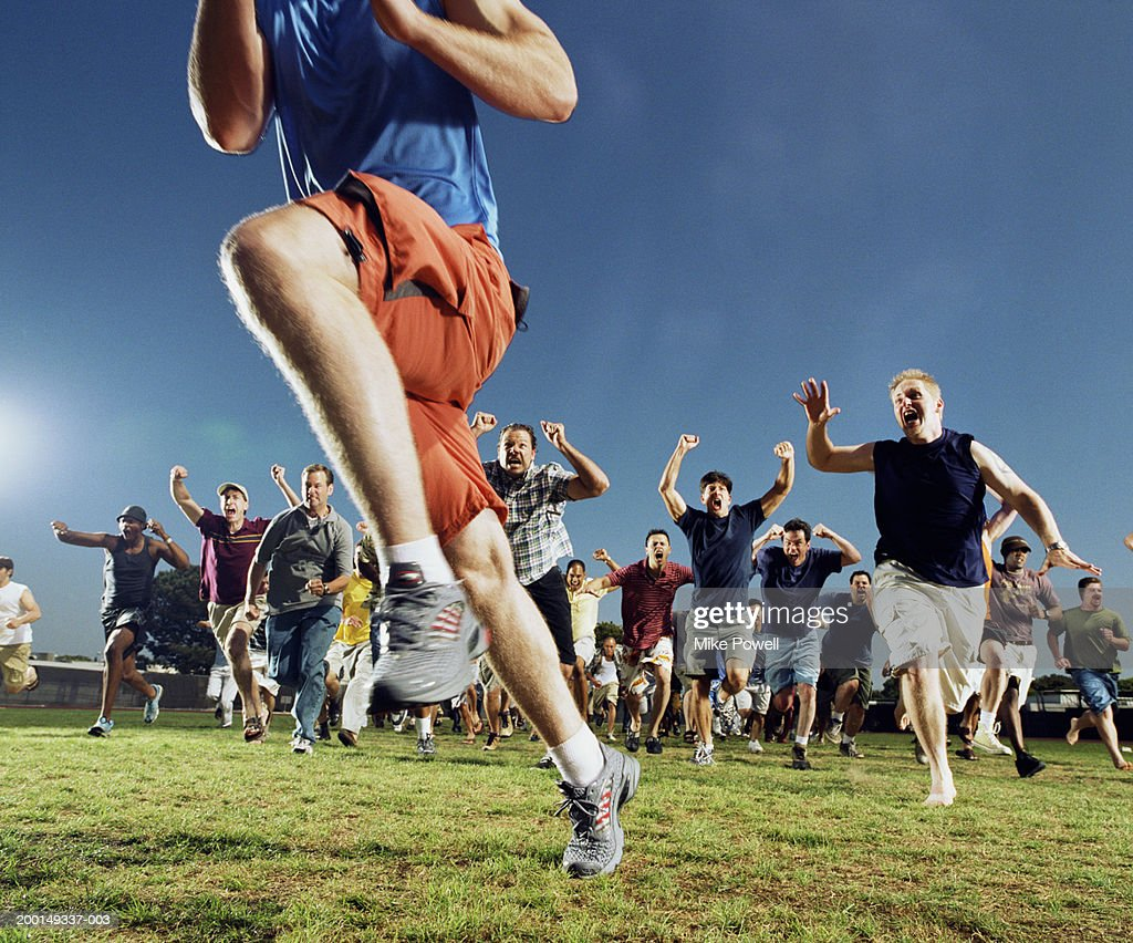 Man being chased by crowd of yelling men : Stock Photo