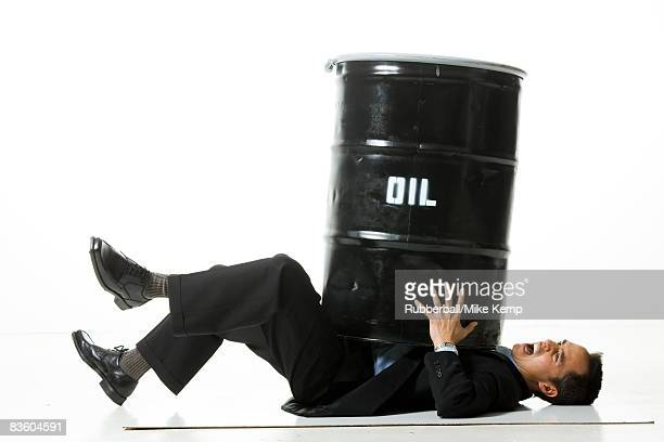 man being crushed by an oil barrel