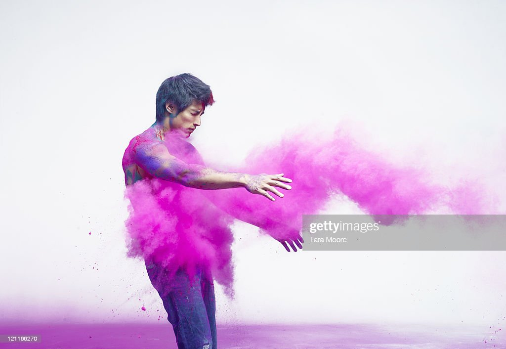 man being impacted by bright pink powder paint : Stock Photo