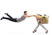 Young man being pulled by a shopping cart full of groceries isolated on white background