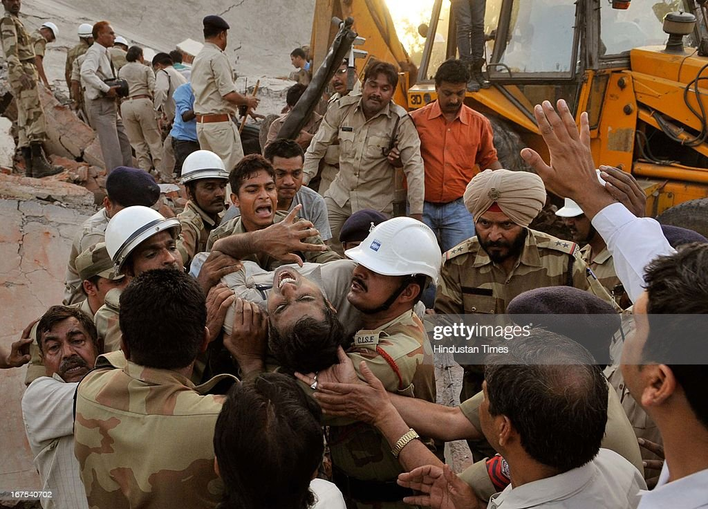 A man being rescued from the debris of the collapsed female medical ward of the Kasturba Gandhi Hospital of BHEL on April 26, 2013 in Bhopal, India. The collapse feared killed at least five persons while about 40 others were trapped in debris, giving rise to fear of more casualties. The rescue work was being carried out on war footing. Kasturba hospital, one of the biggest and oldest hospitals in Bhopal city, provides free treatment to BHEL employees.