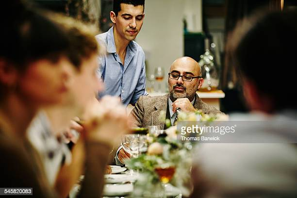 Man being served wine during dinner party