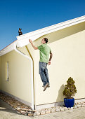 Man being suspended in air, reaching for cat on house roof (digital composite)
