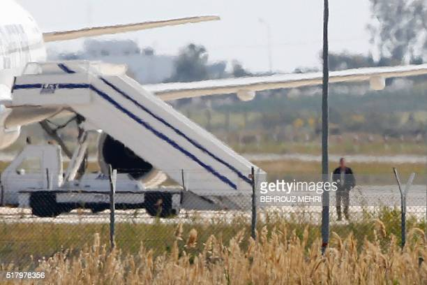 TOPSHOT A man believed to be the hijacker of the EgyptAir Airbus A320 which was diverted to Cyprus leaves the plane on March 29 2016 The hijacker who...