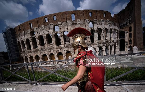 A man belonging to historical groups dressed as a centurion marches along the Colosseum to mark the anniversary of the legendary foundation of the...