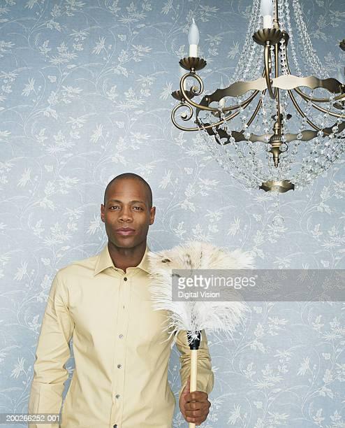 Man below chandelier, holding feather duster, portrait