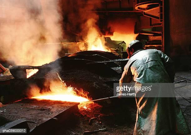Man bending forward, working in blast furnace, rear view
