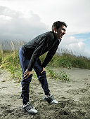 Man bending over on beach