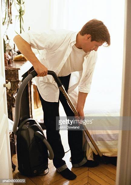 Man bending over, vacuuming, full length