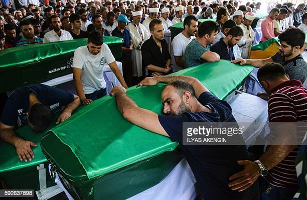 A man bends on a coffin as people mourn during a funeral for victims of last night's attack on a wedding party that left 50 dead in Gaziantep in...
