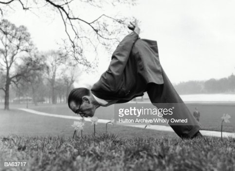 Man bent double smelling daffodils (B&W) : Stock Photo