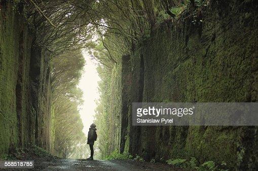 Man between rocks, looking at massive rocky walls