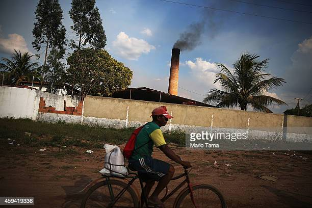 A man bicycles past a ceramics plant that is heated with harvested Amazon wood in a deforested section of the Amazon basin on November 22 2014 in Ze...